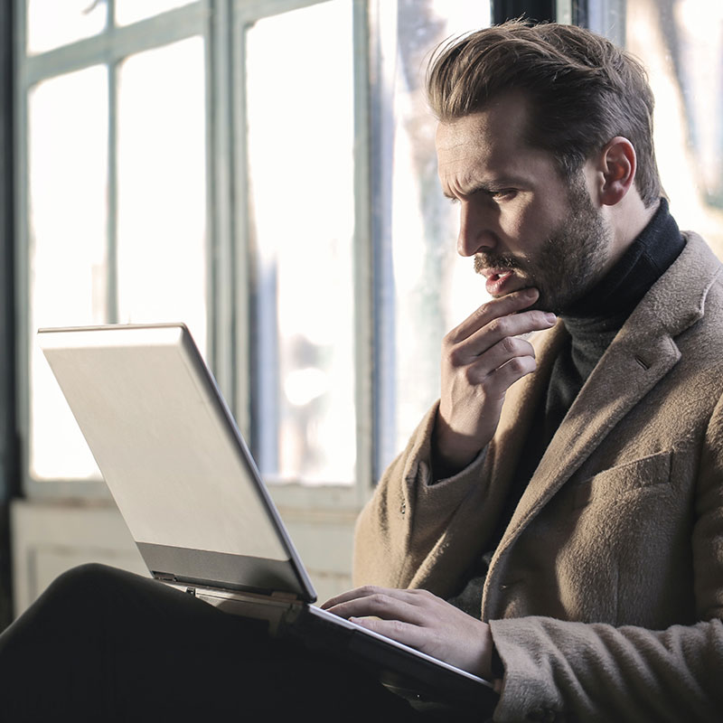 Inquisative Man using laptop; Conceptual Image
